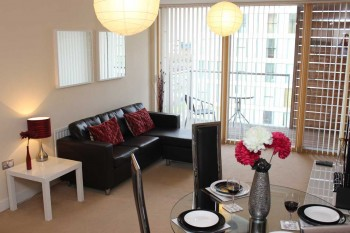 Sofa and dining room table to the open plan serviced apartment with glass sliding door out on to the balcony