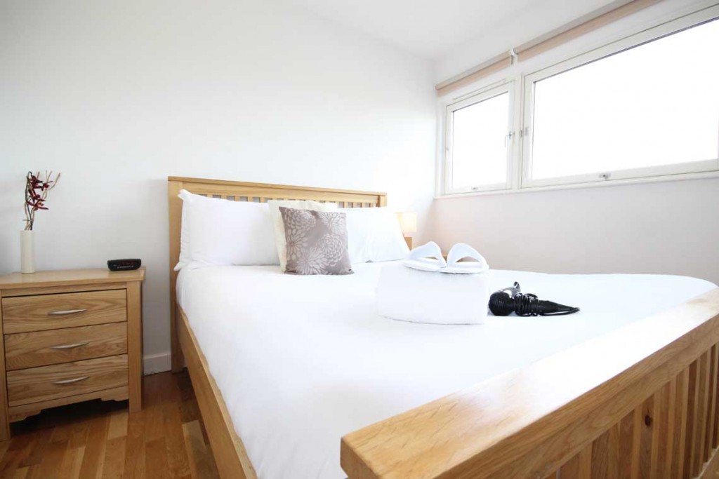 Serviced apartment in Milton Keynes with wooden flooring and crisp white linen